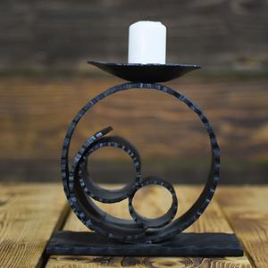 Urokliwy czarny świecznik w kształcie koła, posiadający solidną metalową podstawę.
