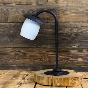 Piękna stylowa lampa na drewnianej podstawce ręcznie kuta