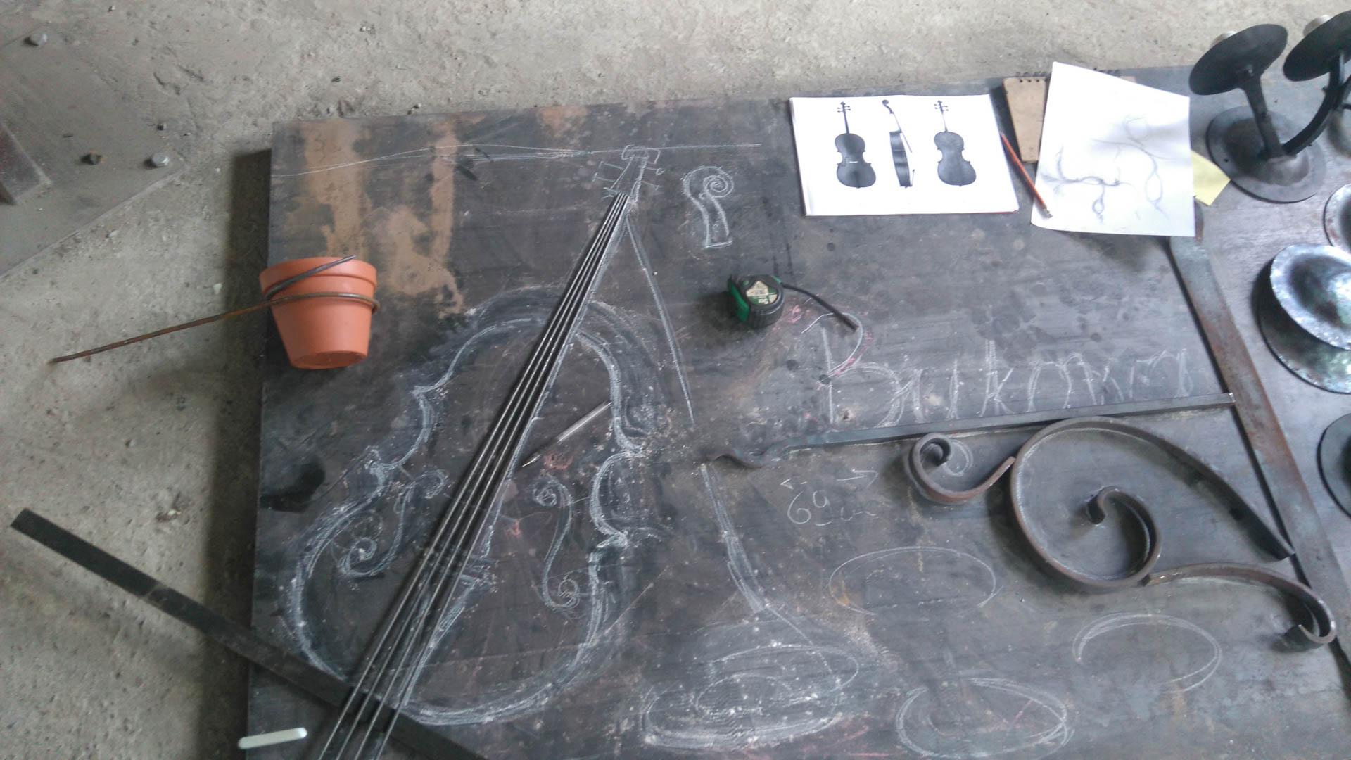 Projekt wykonanego w kuźni skarbów kwietnika kutego ręcznie w kształcie wiolonczeli